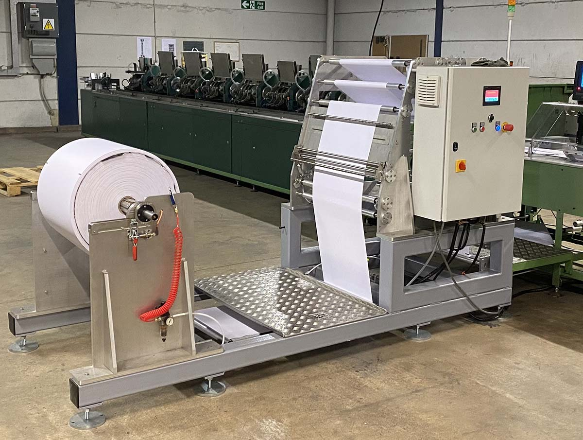 For the Norpak mail wrapping machine to support paper, the feed station required modification to accommodate rolls with a thickness three times higher than the thin plastic film rolls.